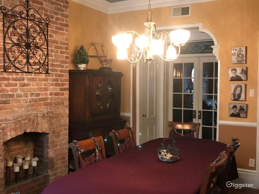 Exposed brick walled dining room with dramatic lighting with ceiling medallion, moulding and textured paint and beautiful rich furnishings