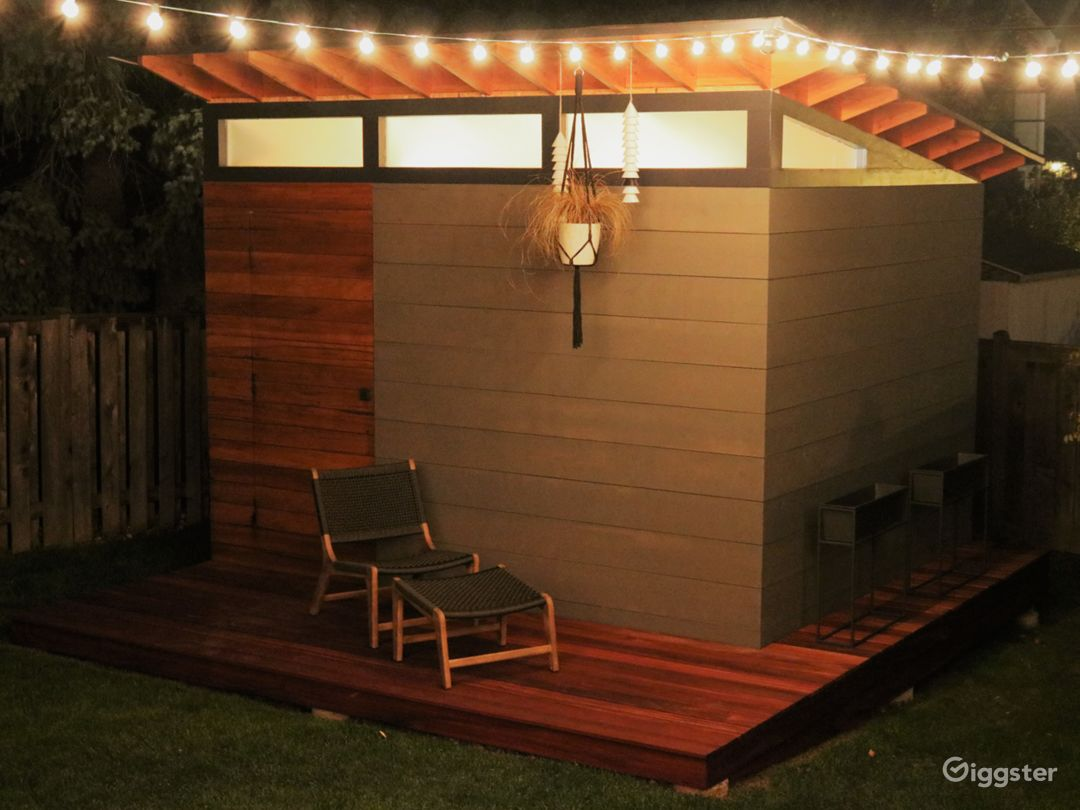 Modern backyard shed with a deck.