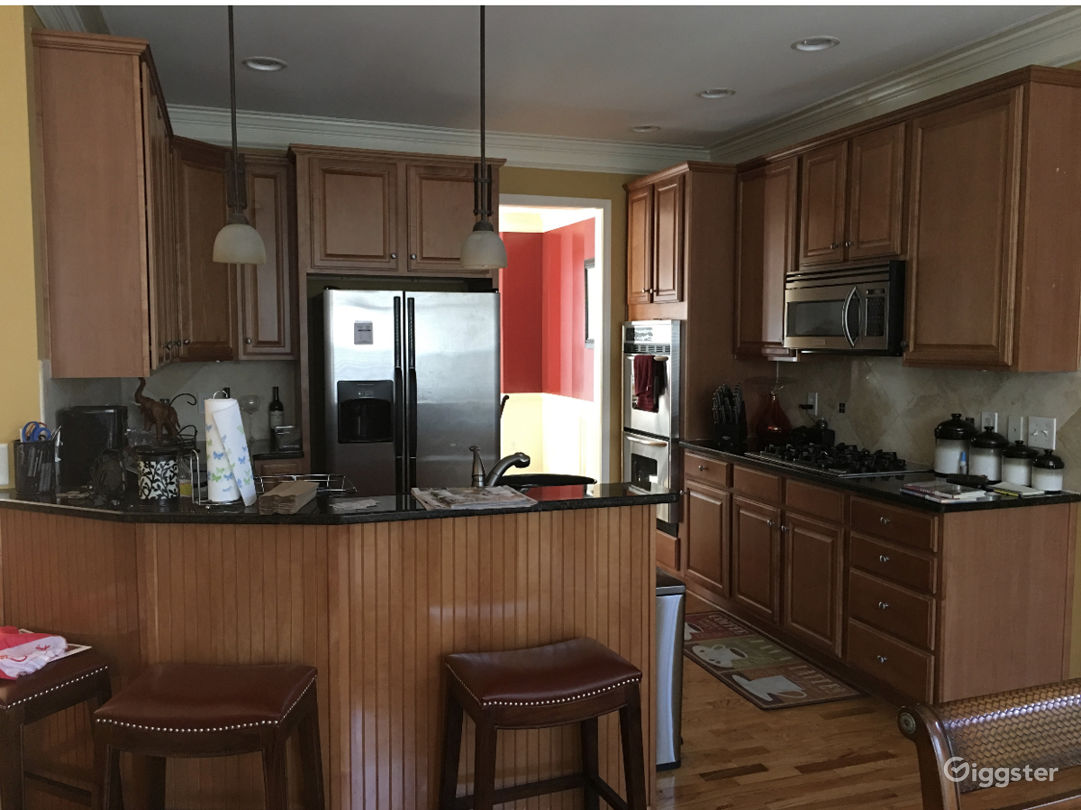 Open kitchen with granite tops, wooden cabinets and stainless steel appliances
