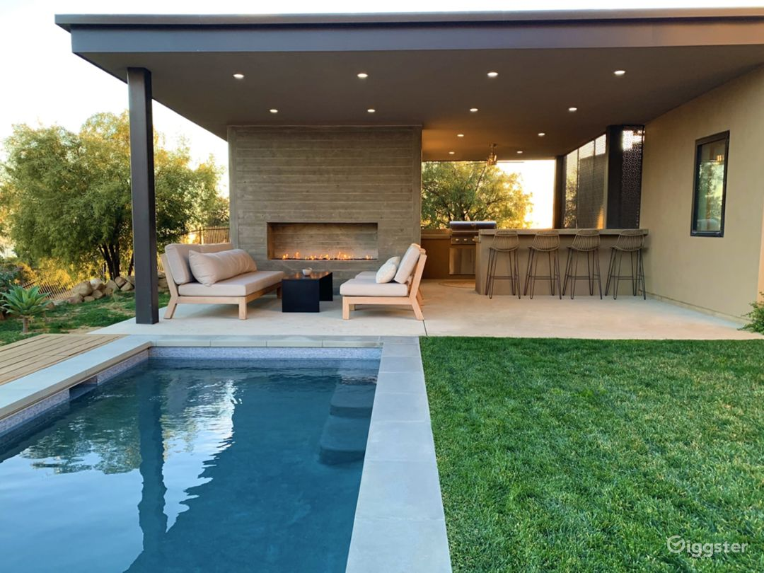Outdoor living area with fireplace, lap pool, outdoor shower, bathroom and outdoor kitchen.