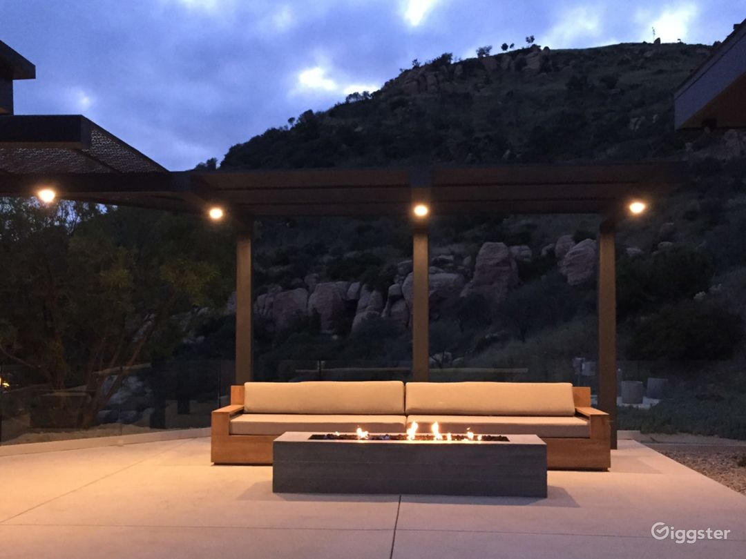 Laser cut steel shade structure/pergola with fire pit and rock formations.