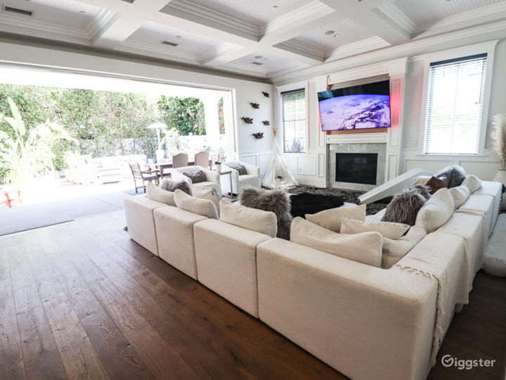 Living room features coffered ceilings and indoor/outdoor living evocative of the Southern California lifestyle.
