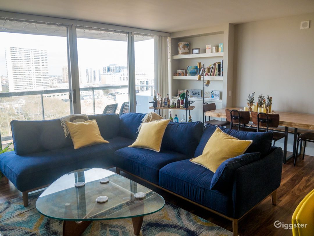 Gorgeous living room with mid century furniture and a custom built dining room table. Tons of natural light thanks to floor to ceiling windows and an 18th floor balcony with views of the city.