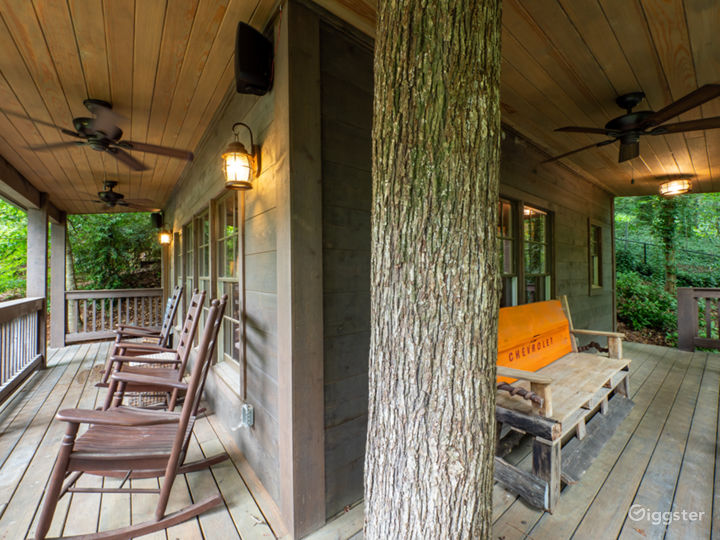 Wrap around porches with rocking chairs, bench and actual tree the cabin was built around