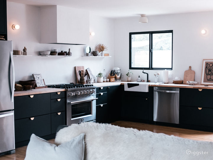 Open kitchen with matte black lower cabinets, light butcher block counter tops and custom plaster range hood.