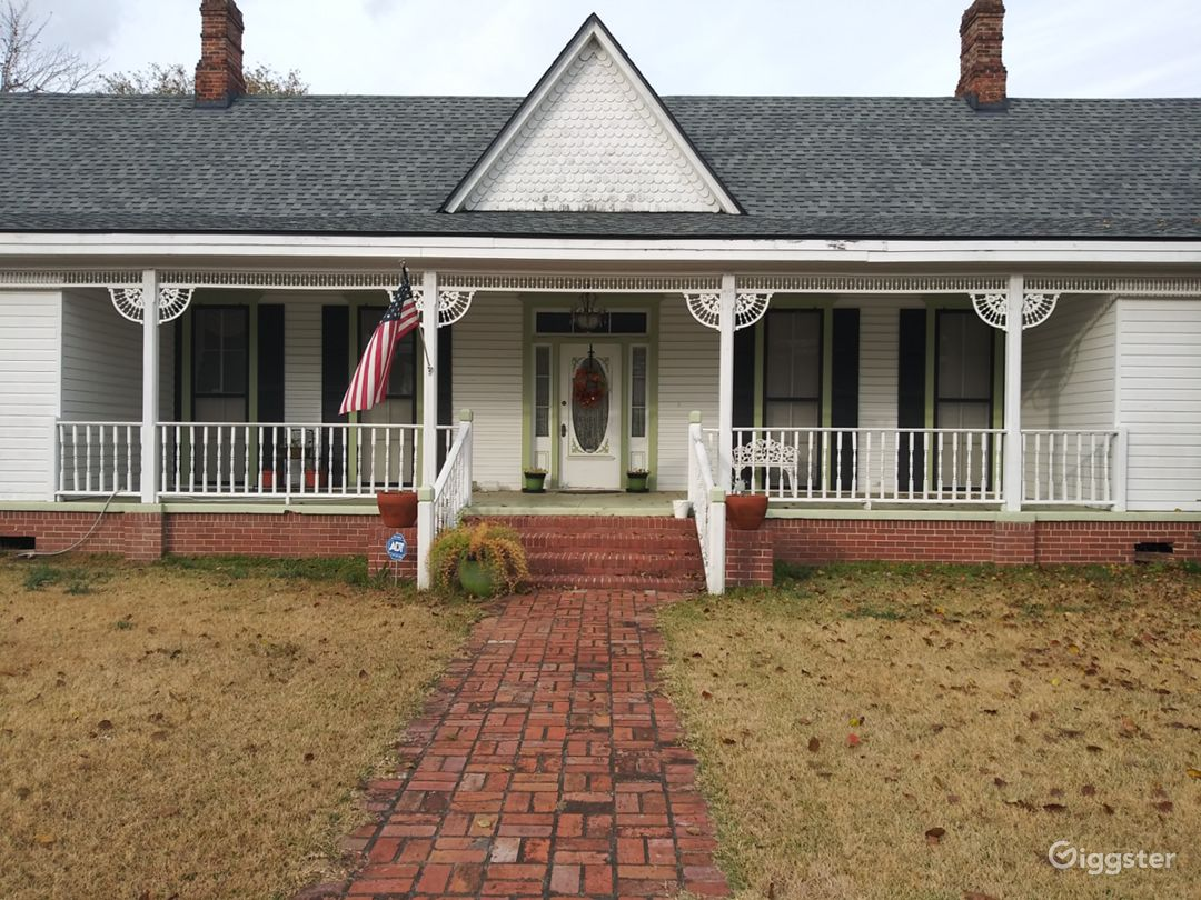 Front of house.  Brick sidewalk and white picket fence.