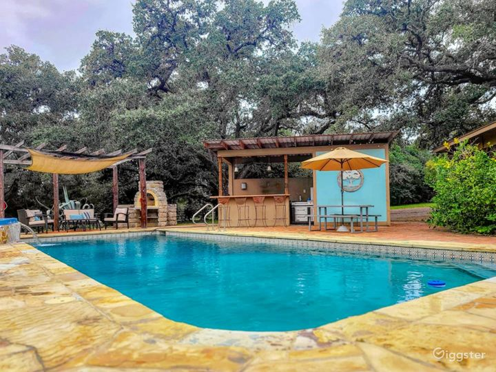 Pool area with hot tub, pergola, pizza oven, and outdoor kitchen