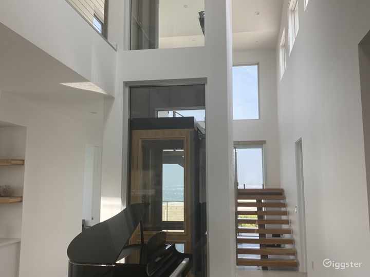 Glass elevator, floating stairs, baby grand
