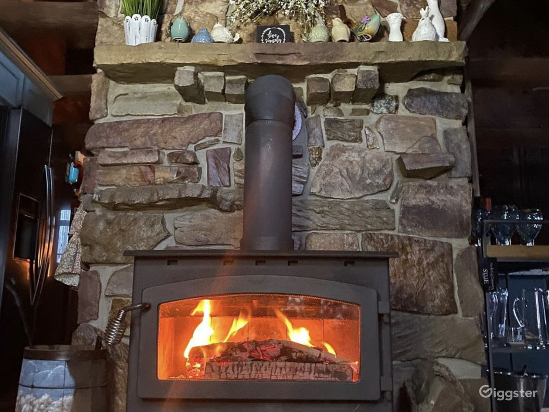 Cozy wood burning, two story fireplace crafted from stones right from the property.