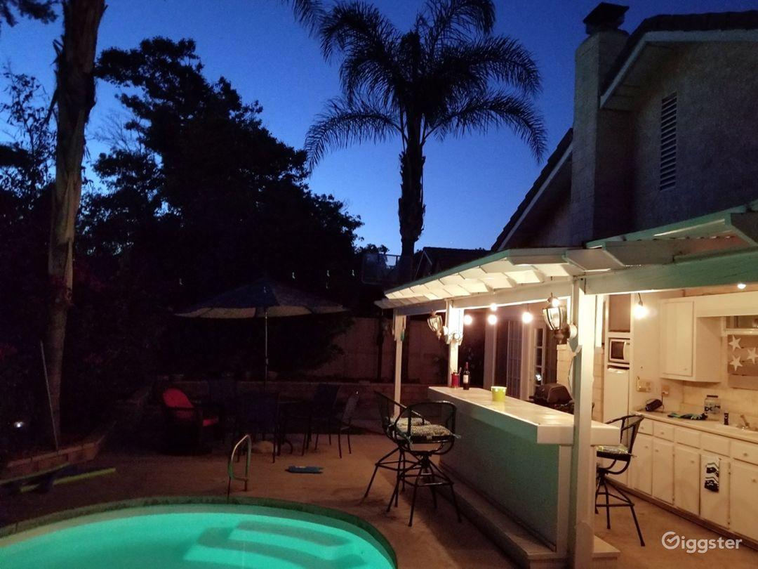 Backyard pool patio. Mature palms, pool, hottub, bar.