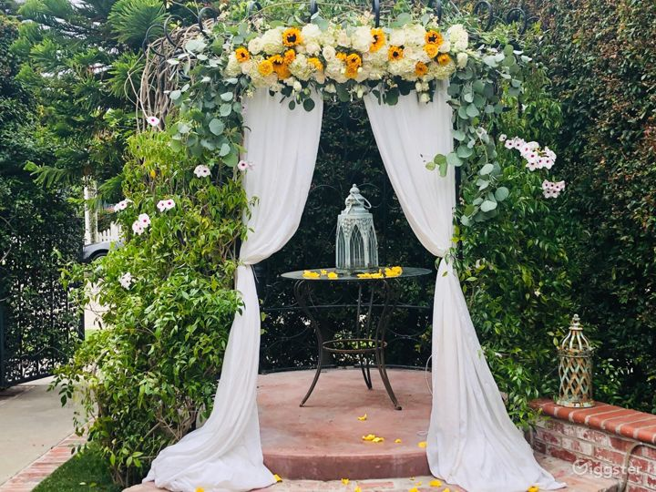 The garden is set up with an English garden style theme including a beautiful gazebo with crystal chandelier, fountain, climbing roses and brick style flower planter.