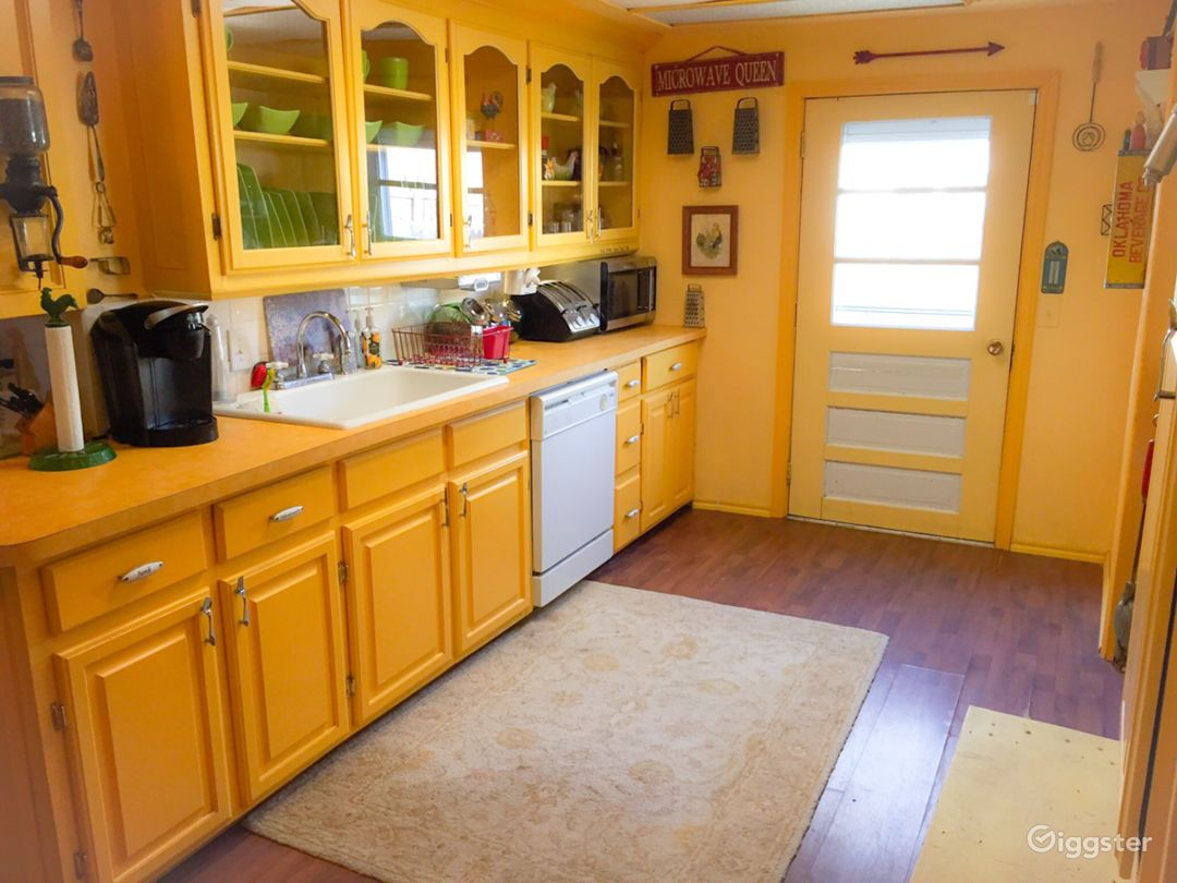 The kitchen also features cabinets with glass doors, salvaged antique lights and metal ceiling tiles