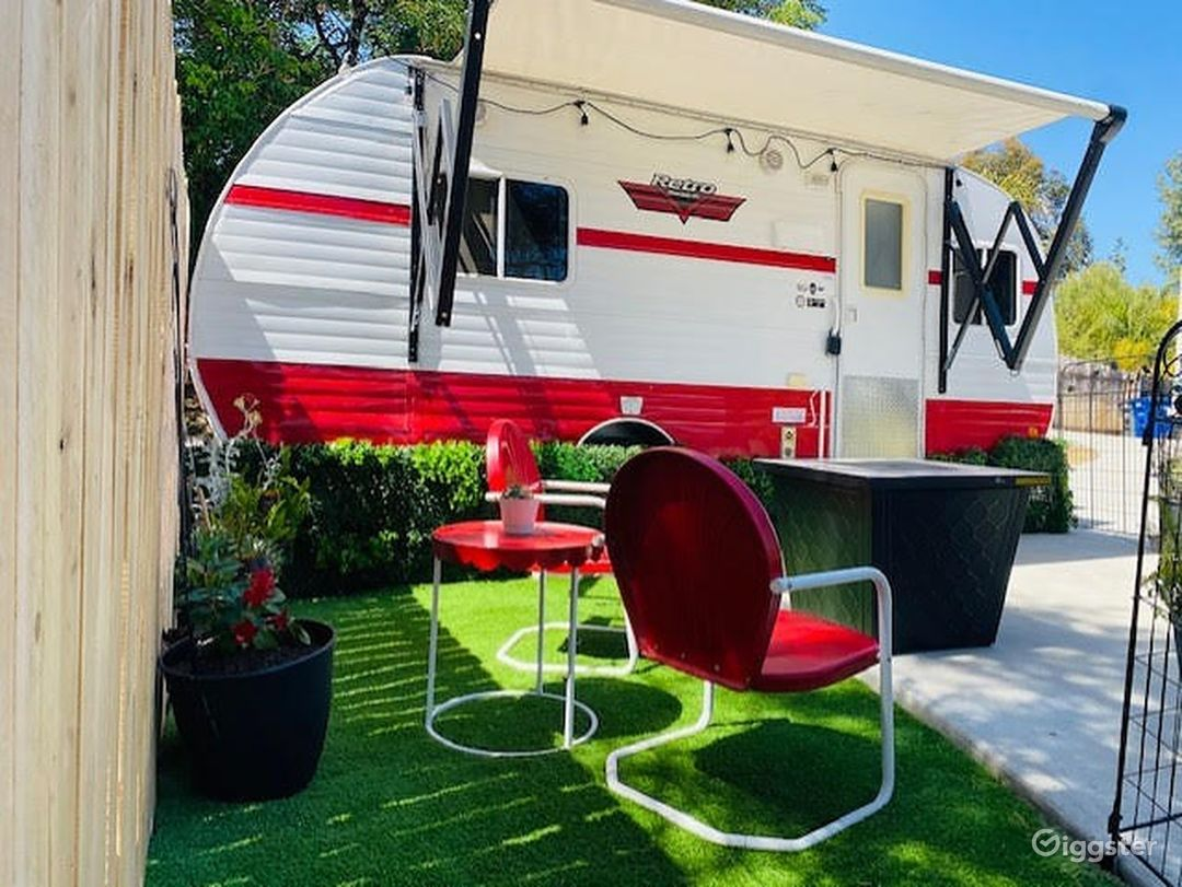 Exterior of Miss Ruby Red with vintage chairs, small yard and fire pit