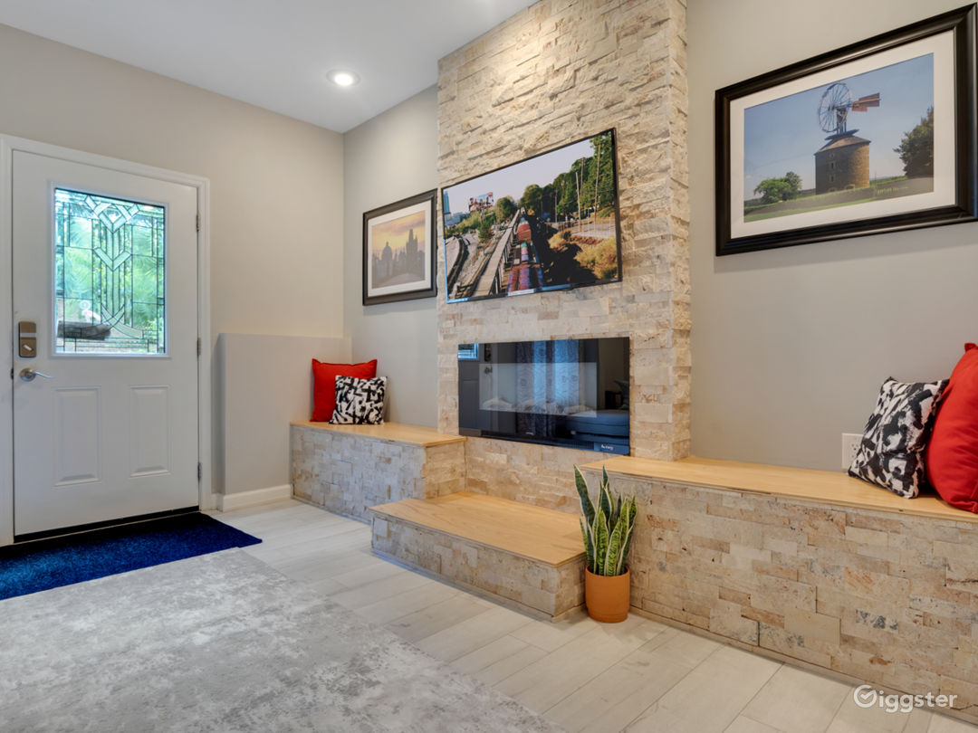 Stacked stone electric fireplace with seating and smart Tv