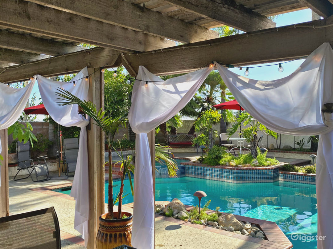 Patio overlook with stylish curtains on gorgeous large pool and tropical landscape.