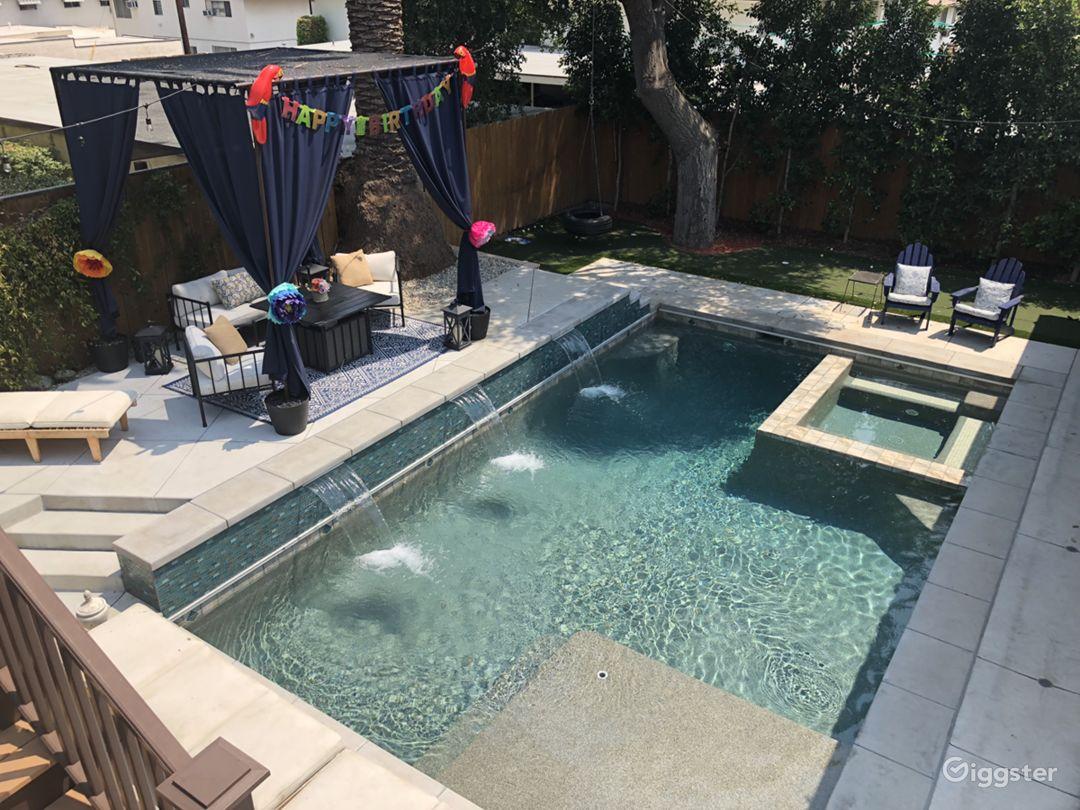 Backyard pool and jacuzzi with cabana and waterfalls