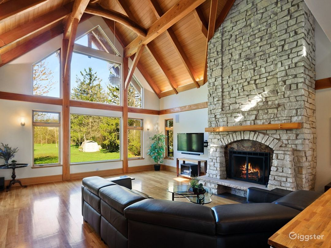 Main Residence Great Room with white oak radiant heated floors, stone and slate wood burning fireplace and vaulted, heavy timber ceiling with uplighting.