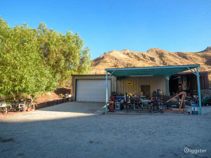 Front of working mechanics shop complete with street rods and tools
