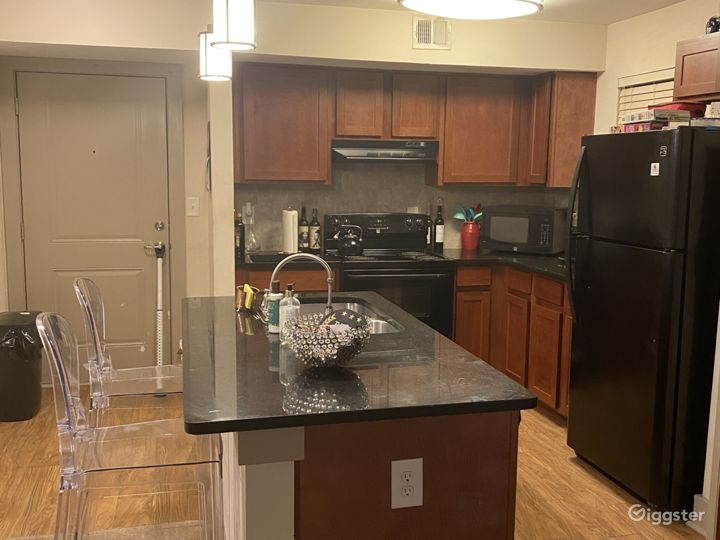 Open kitchen with an island, granite countertops, full stove, full fridge, and hardwood flooring.