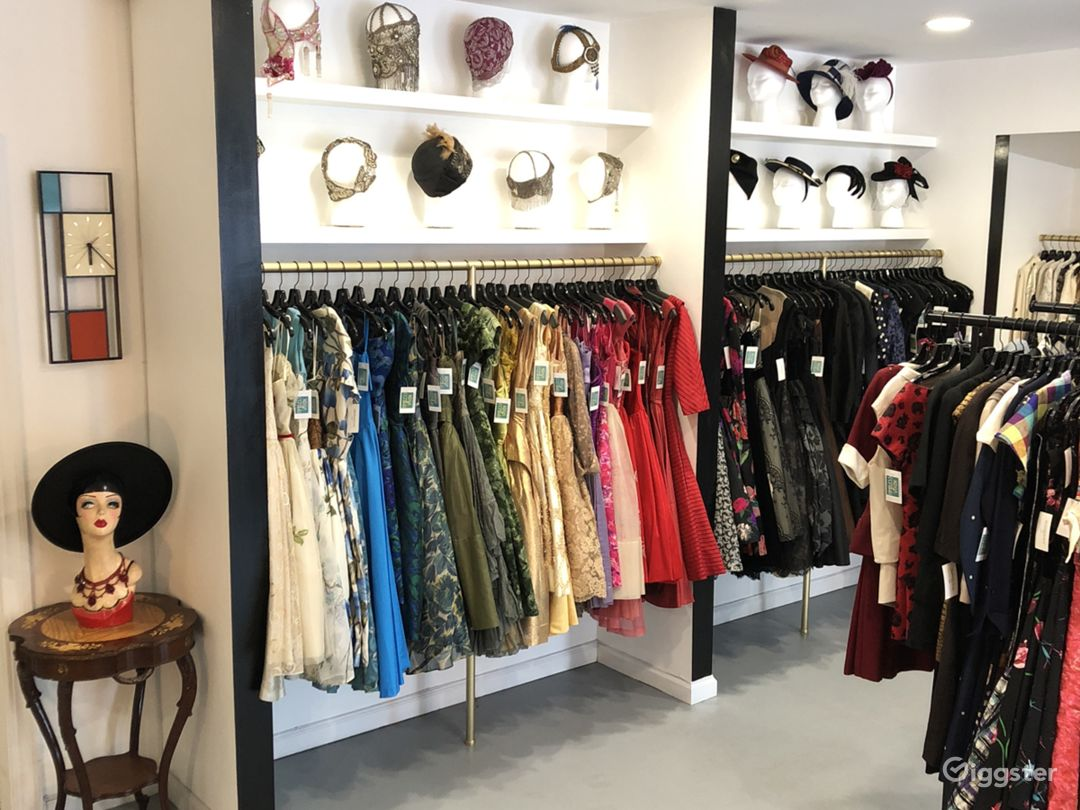 Wall of 50's party dresses, 20's headpieces and 40's hats