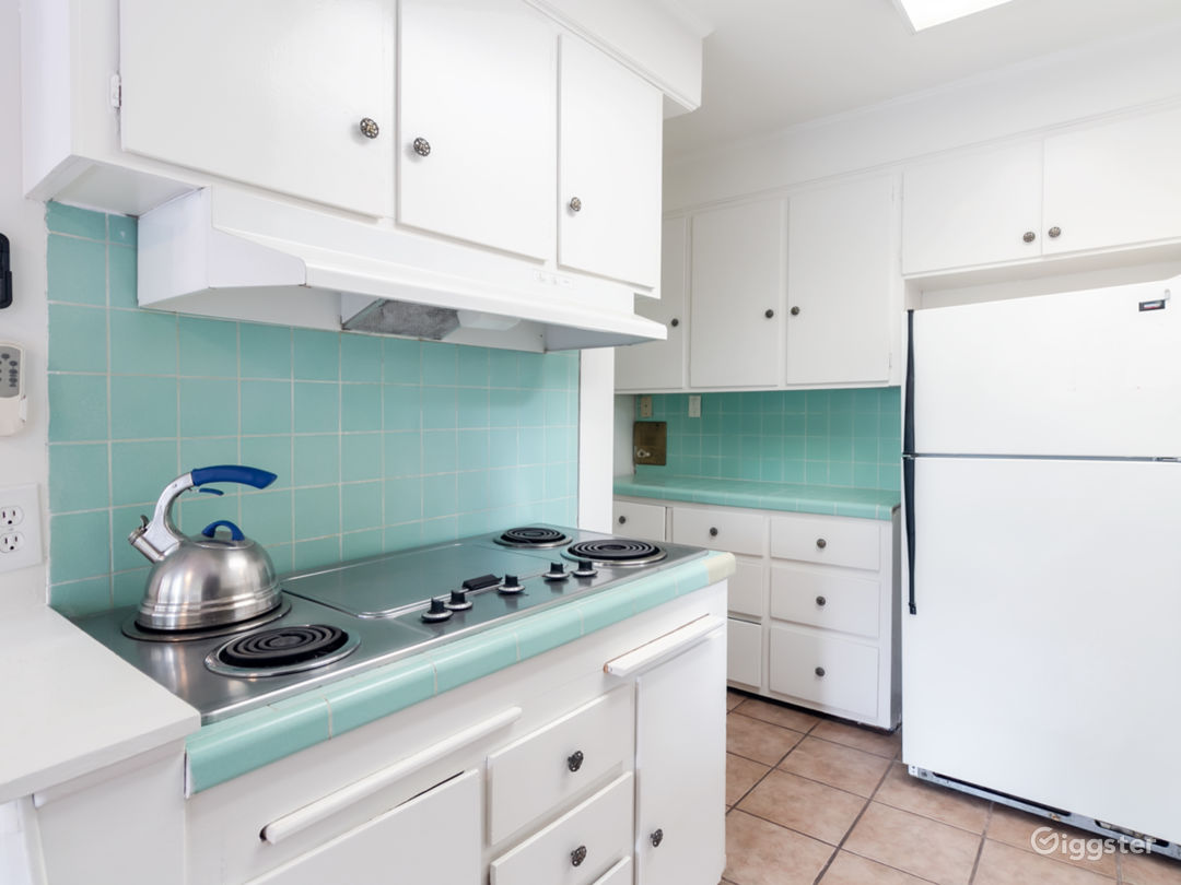 Retro turquoise blue tiled kitchen with tile floor, original cabinets, cook top stove, louver window over sink, refrigerator and dishwasher.