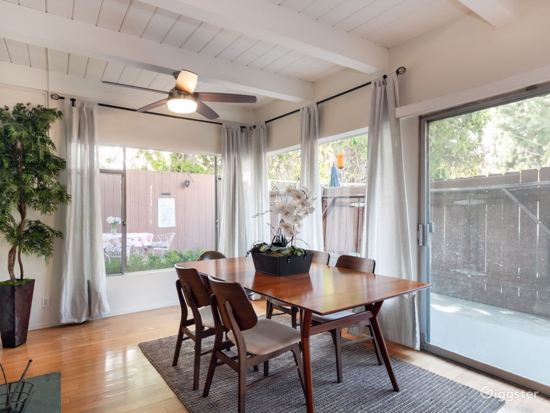 Separate large dining room leading to retro kitchen with walls of glass overlooking private wraparound fenced private yard