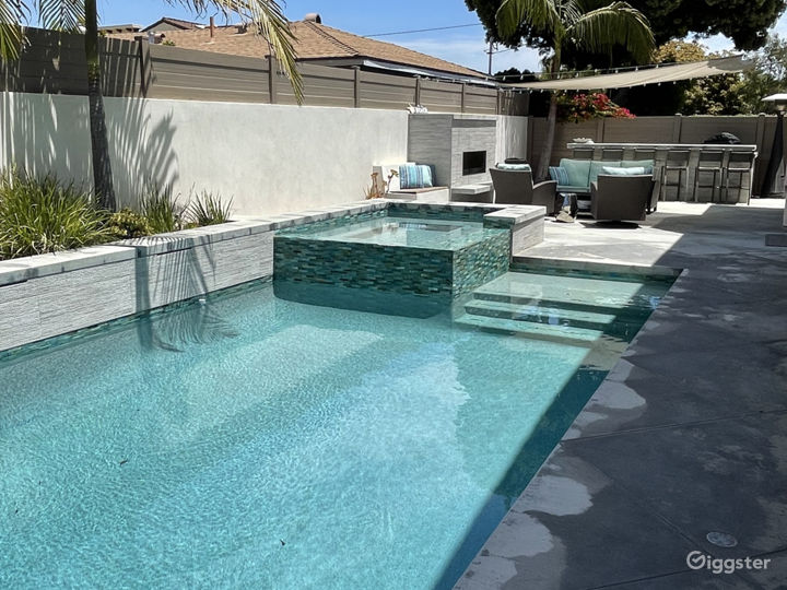 Pool and spa with water feature and LED color lights.