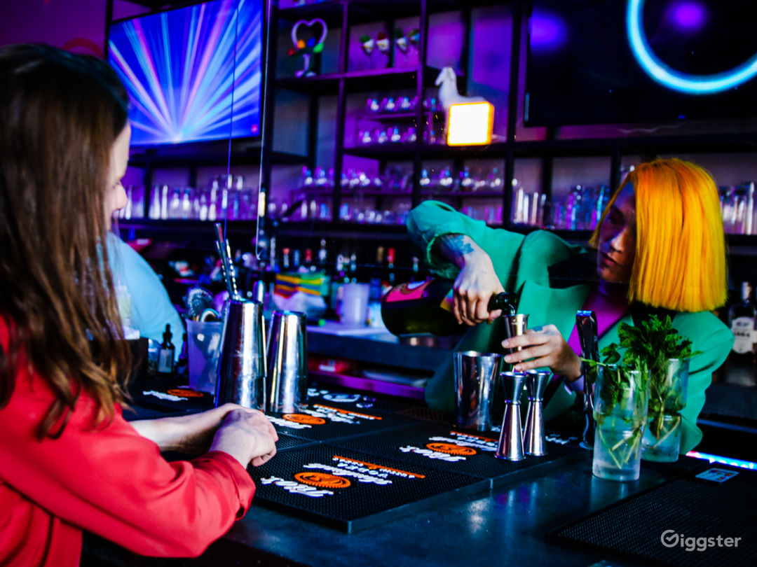 Large L-shaped concrete bar with TVs and lighting