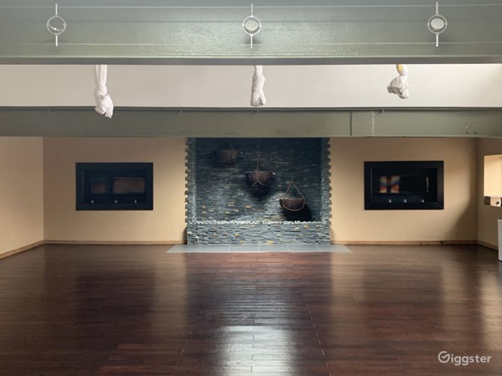 Main studio space with exposed beams, custom waterfall wall, in-laid gas fireplaces and aerial silks (they can be removed)