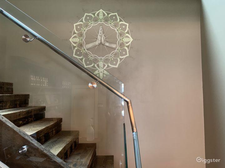 custom mandala mural in lobby with reclaimed wood stairs heading to 2nd floor studio spaces