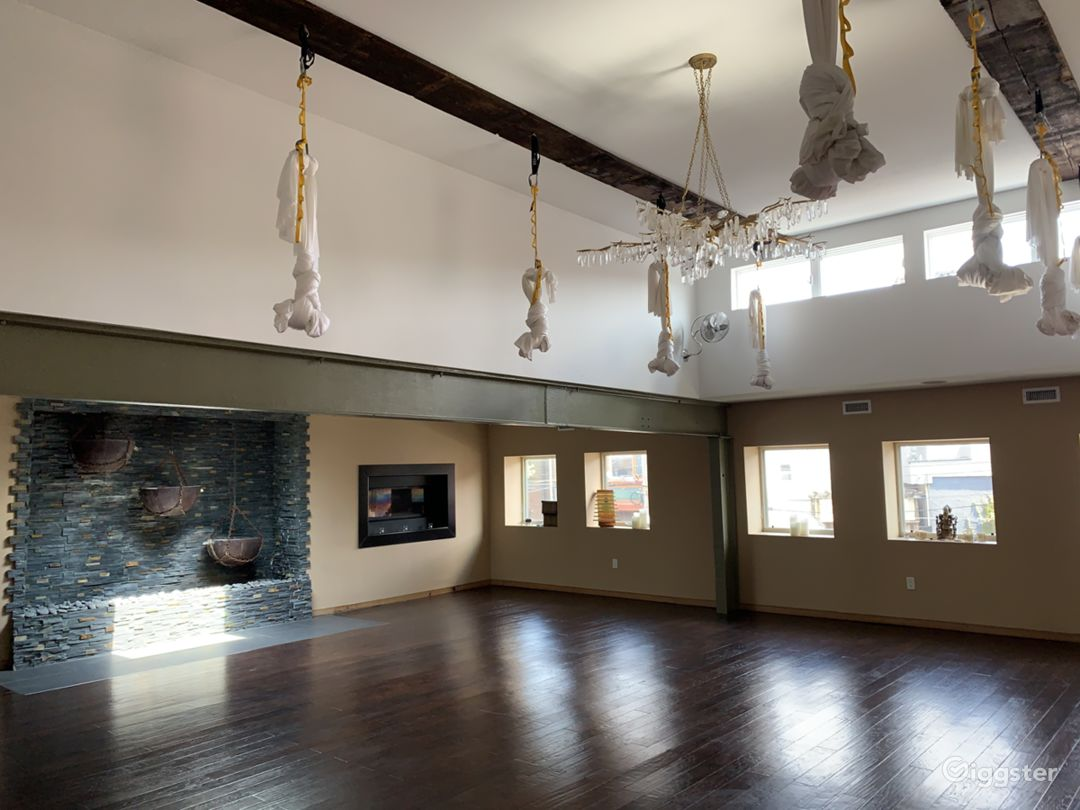 Main studio space with exposed beams, high ceilings, skylights (there are 2 other that are not visible in pic), custom waterfall wall, in-laid gas fireplaces crystal chandelier and aerial silks (they can be removed)