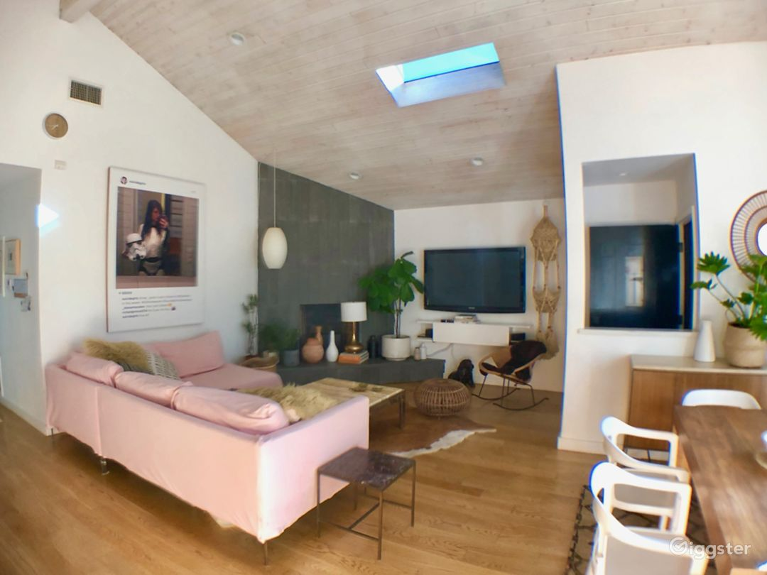 Living room, 16' ceiling, hardwood floors, slate fireplace. Sofa has pink OR white covers.