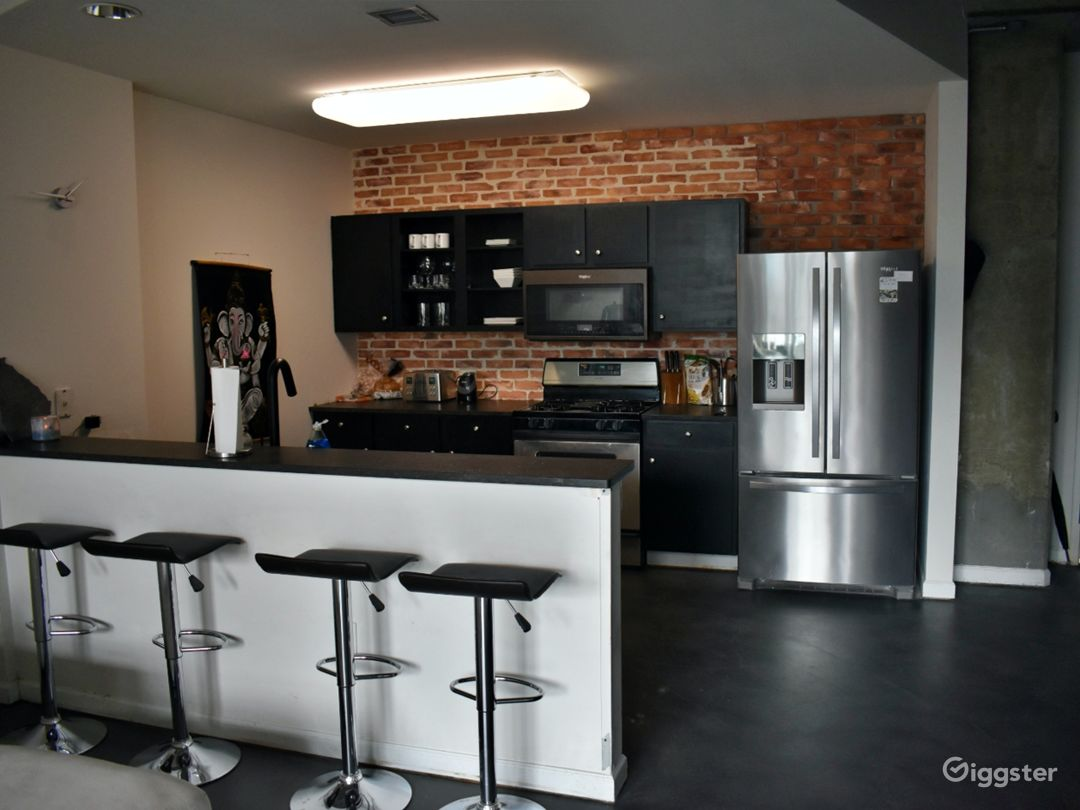 Newly renovated kitchen with real brick wall and custom granite counters