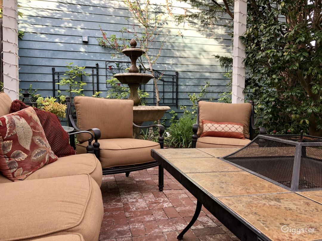 Seating area includes wrought iron sofa, four chairs, pillows and tiled firepit table