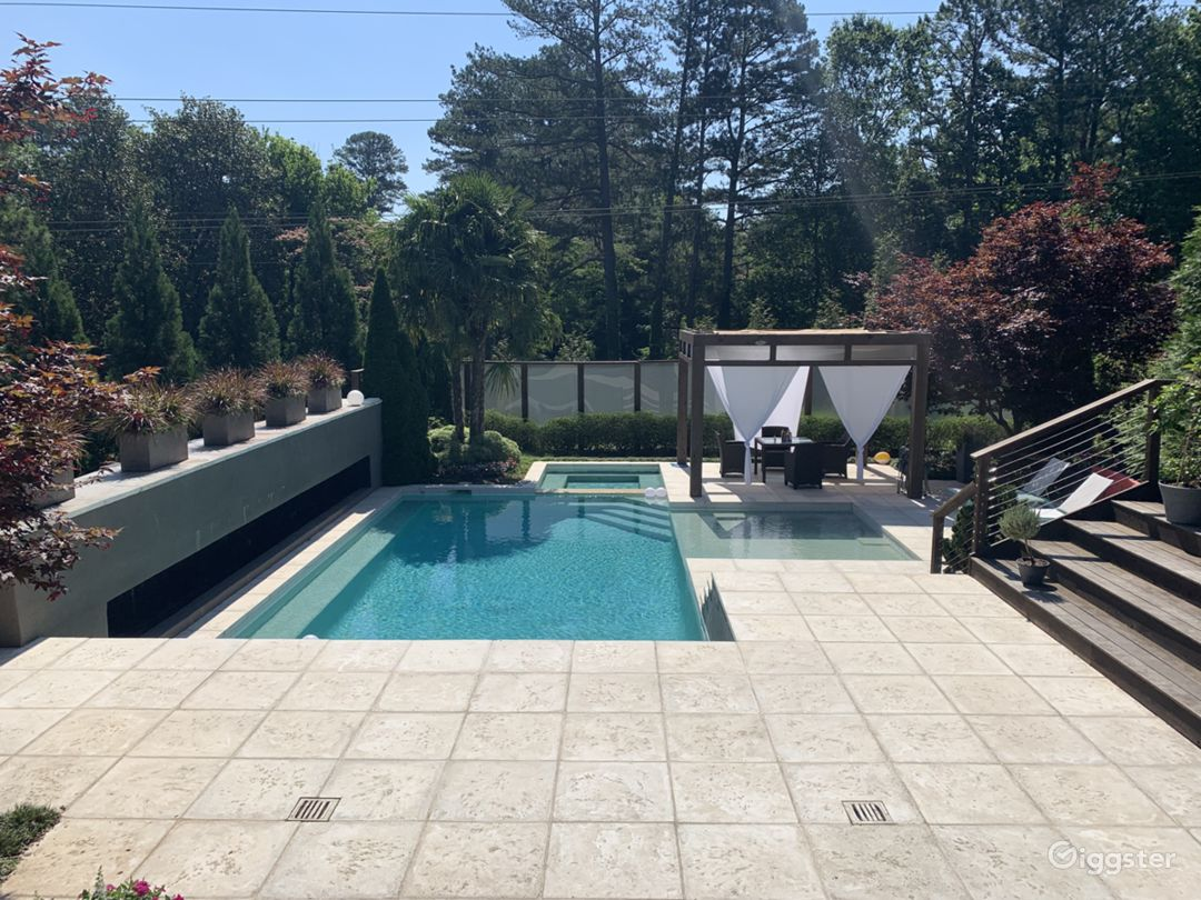 Looking from the living area through the sliding glass doors to the pool area which contains an outdoor fireplace on the left.  This is the entrance to a 4 room outdoor space that is one of the most versatile outdoor spaces in Atlanta.