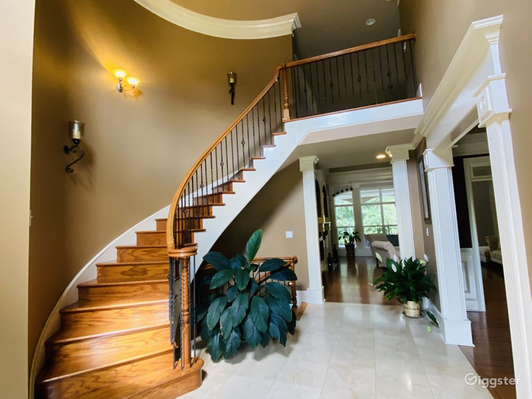 Foyer with an open view of the upper level, dining room and family room.