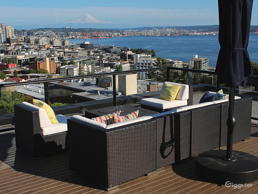 Great rooftop view of city and Elliott Bay including a firepit, custom kitchen, lounging and eating areas