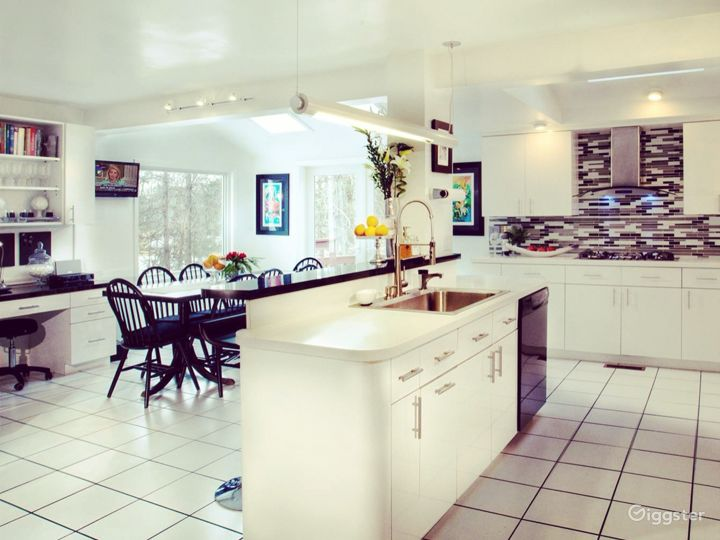 Large, white, open floor plan kitchen with island seats 10 at table plus 2 at counter