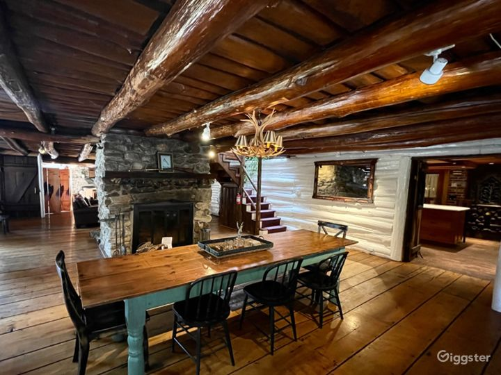 Open dining area highlighted by wood burning, stone fireplace, exposed log cabin ceiling and stunning wide planked wood flooring.