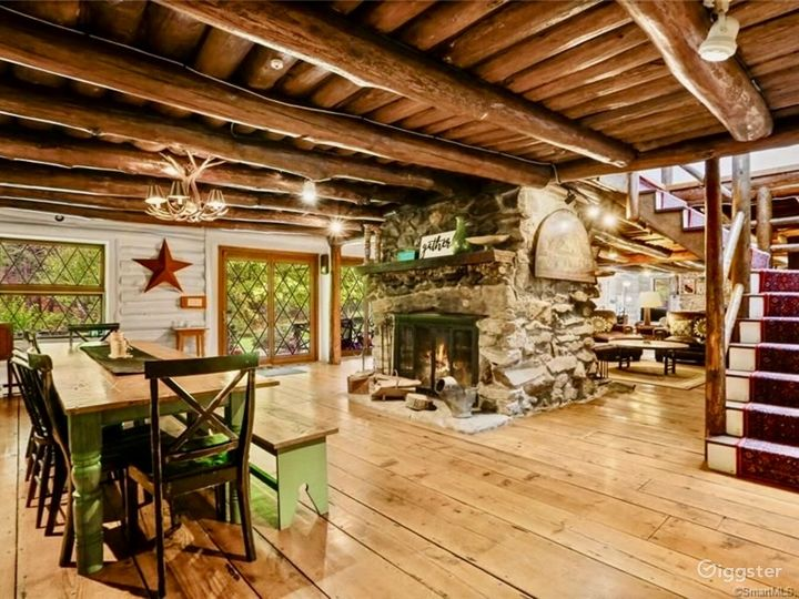 Dining area with charming log cabin stairs case leading to four bedrooms and three baths on second floor.