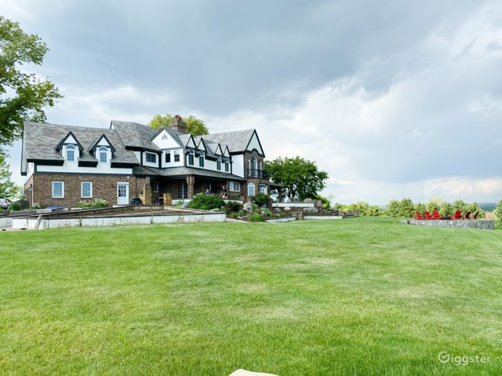 Back exterior with a bluestone patio that spans the entire back of the home.  Mature gardens and lovely firepit area.  Flat level wide open yard.