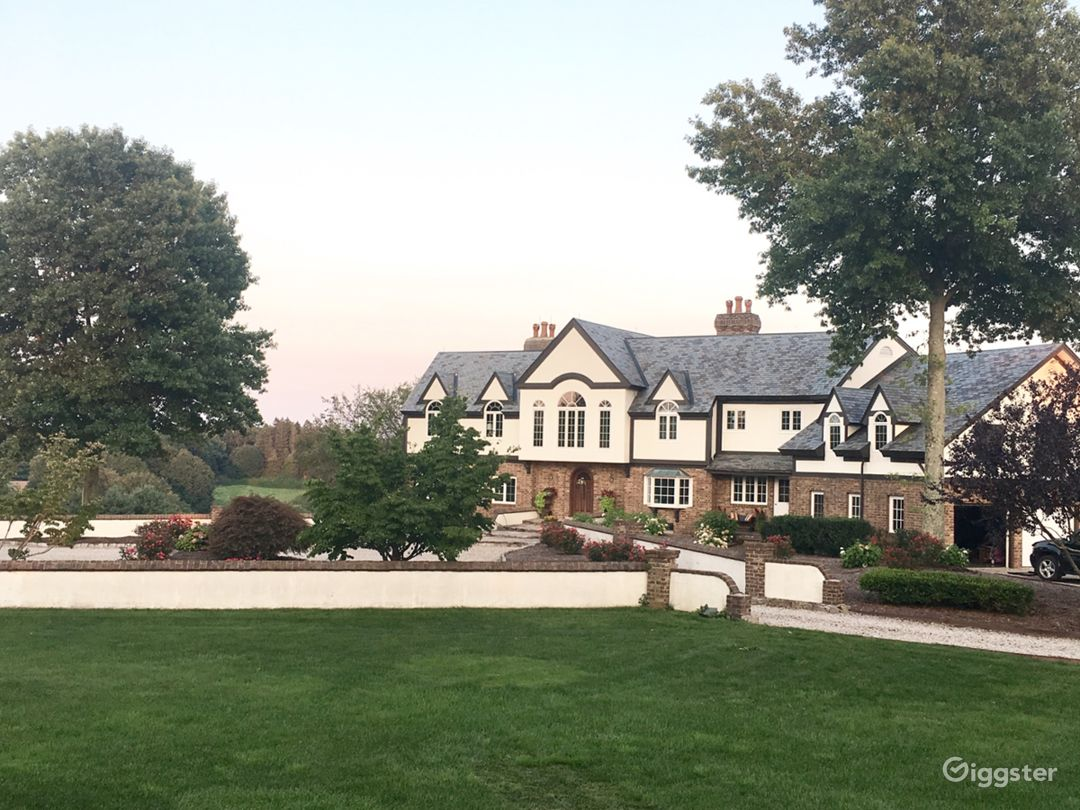 Front exterior with gravel circular driveway.  Mature rose and hydrangea gardens.