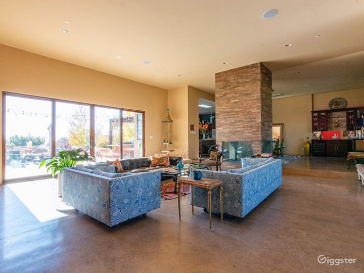 Open concept living, dining, kitchen area with sliding glass doors to patio/courtyard.  Four sided glass and stone fireplace.