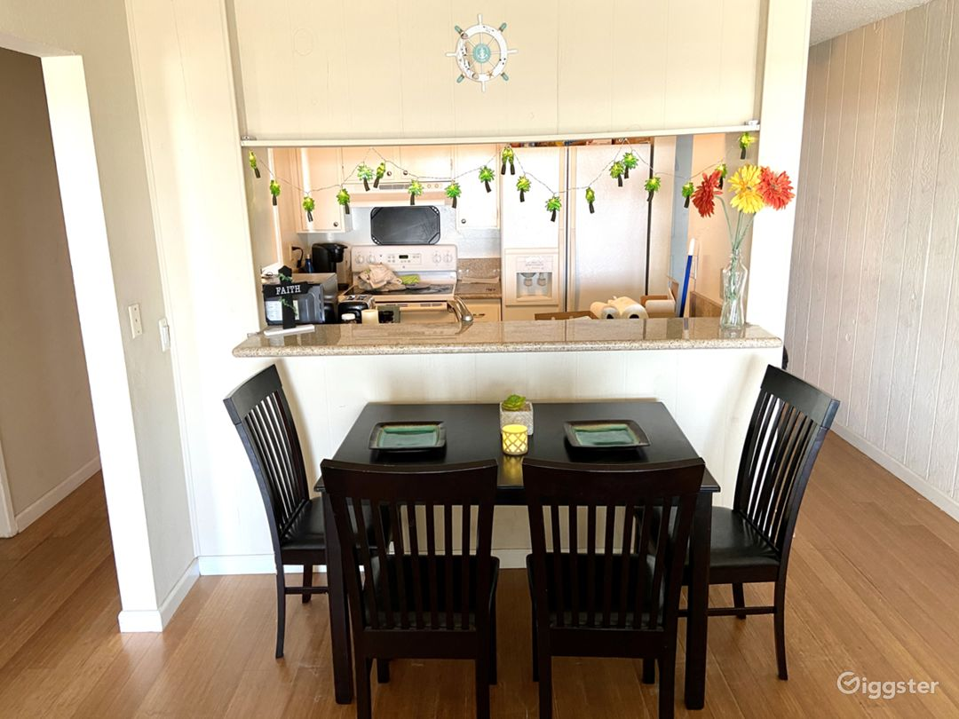 Small dining table and open kitchen with full appliances