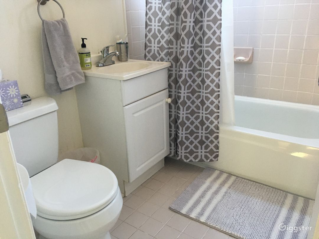 50's bathroom with wainscot walls and tiled floors.