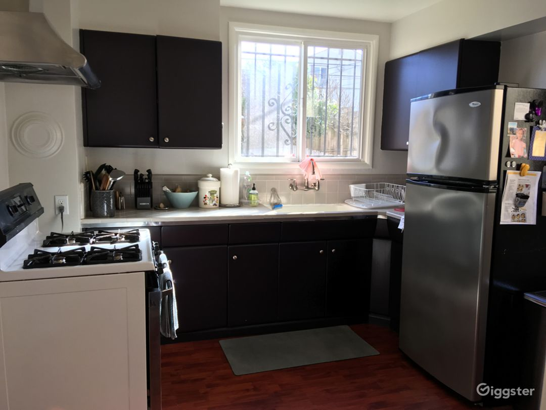 50's kitchen with updated paint job on metal cabinets with cherry-stained laminate floor.