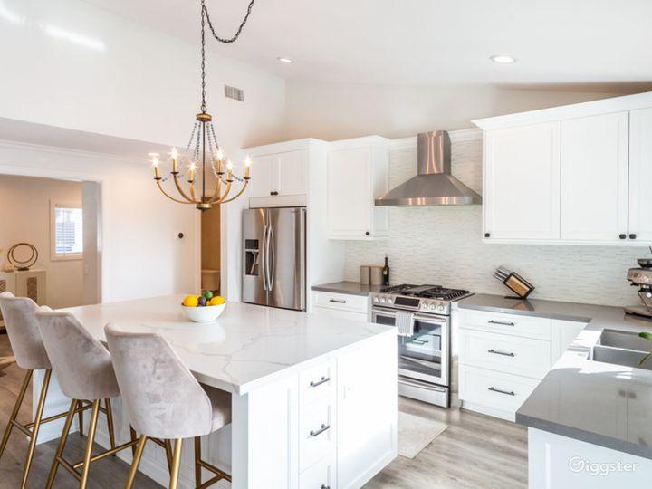 White kitchen with large island and bar stools