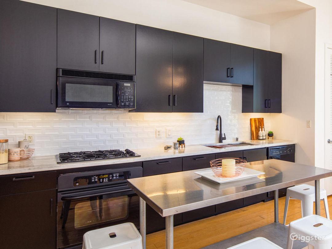Fresh remodel with black cabinets, marble counters and porcelain beveled tile backsplash