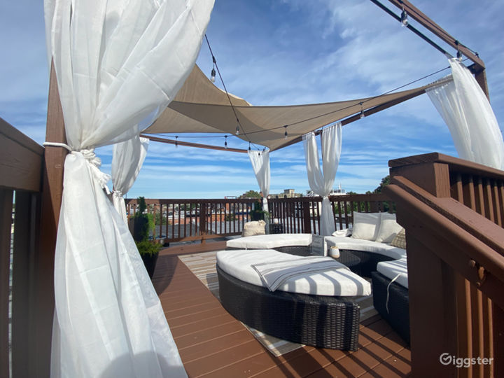 Cabana style rooftop deck with city views features luxury daybed