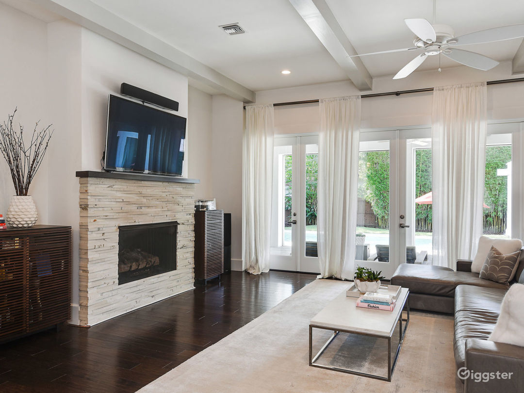 Living Room with stone fireplace, doors open to outdoor entertaining